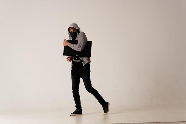 Een man met een monitor in zijn handen steelt een computeranonimiteit hackerstudio