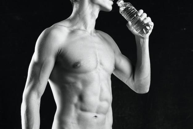 Een man met een opgepompt lichaam bedekt zichzelf met een handdoek studio fitness