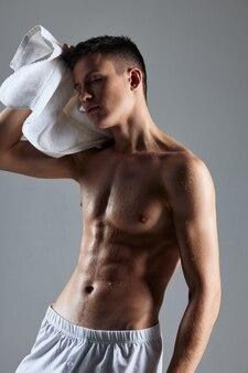 Een man met een opgepompt lichaam veegt het zweet van zijn vermoeidheid van zijn gezicht af. hoge kwaliteit foto