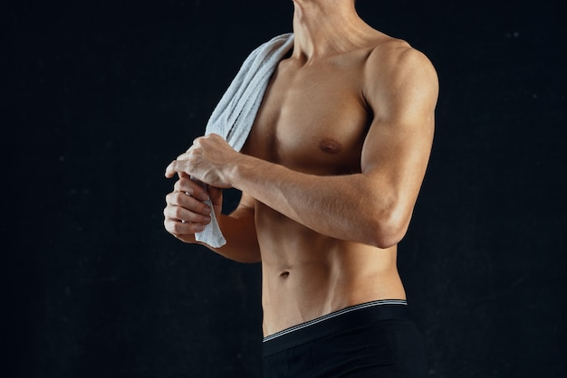 Een man met een opgepompte pers in zwarte korte broek gym donkere achtergrond