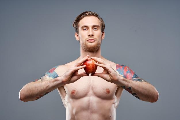 Een man met een opgepompte torso en een tatoeage houdt een appel in zijn handen op een grijze achtergrond