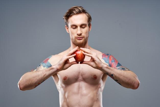 Een man met een opgepompte torso en een tatoeage houdt een appel vast
