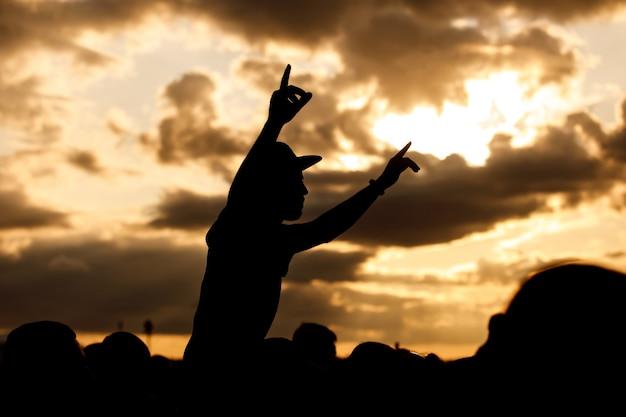 Een man met een pet en opgeheven armen geniet van een openluchtmuziekfestival. zwart silhouet op zonsondergang.