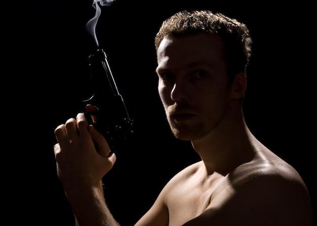 Een man met een pistool en rook over het pistool op zwarte achtergrond
