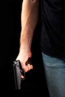 Een man met een pistool in zijn hand op een zwarte achtergrond. moordenaar met een pistool