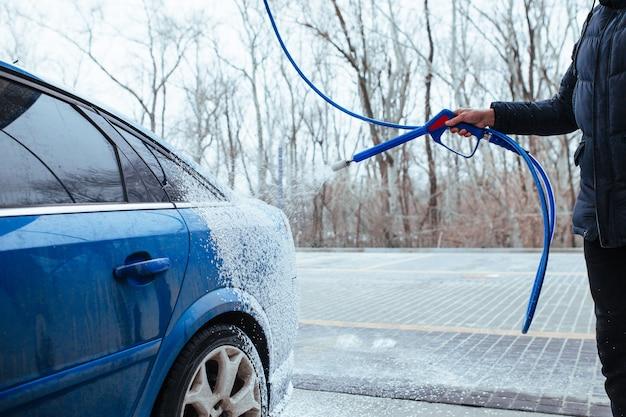 Een man met een pistool om schuim op de auto aan te brengen. self-carwash