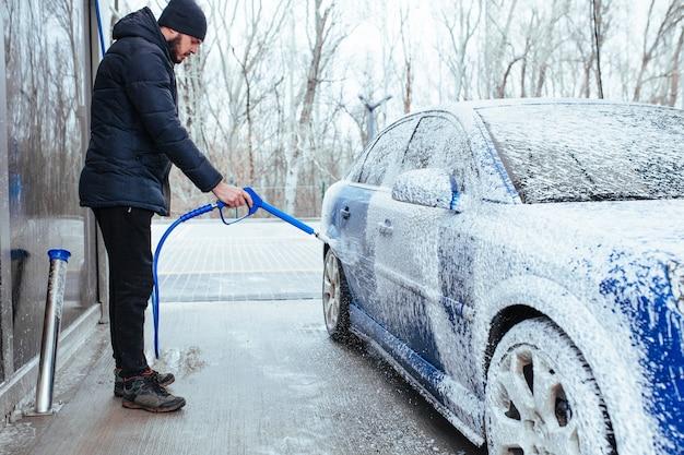 Een man met een pistool om schuim op de auto aan te brengen. zelfbediening carwash