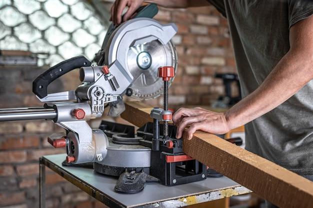 Een man met een plank en mijter zag close-up, concept bouwen en repareren.