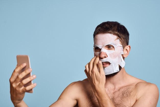 Een man met een reinigingsmasker op zijn gezicht onderzoekt zichzelf in een spiegel op een blauwe achtergrond