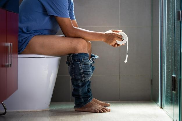 Een man met een rol wc-papier in het toilet