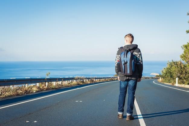 Een man met een rugzak loopt alleen op een bergweg