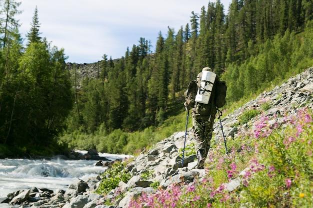 Een man met een rugzak loopt langs een bergrivier.