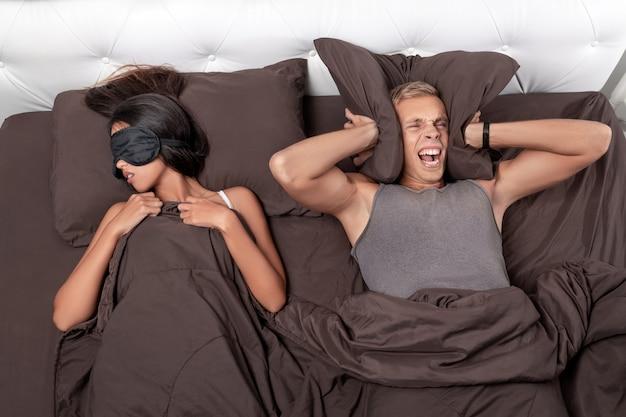 Een man met een schreeuw knijpt in zijn hoofd met een kussen terwijl hij probeert te slapen, terwijl zijn vriendin lekker slaapt