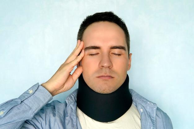 Een man met een slechte nek in een zwarte halsband om de halswervels te stabiliseren. een man met een nekletsel op een blauwe achtergrond. wervelfractuur. hoofdpijn.
