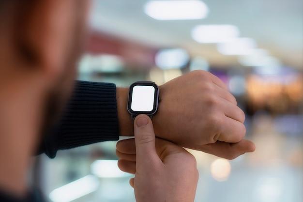 Een man met een smartwatch en een mockup met een wit scherm op zijn hand. een man gebruikt een fitness-tracker op de achtergrond van een winkelcentrum.