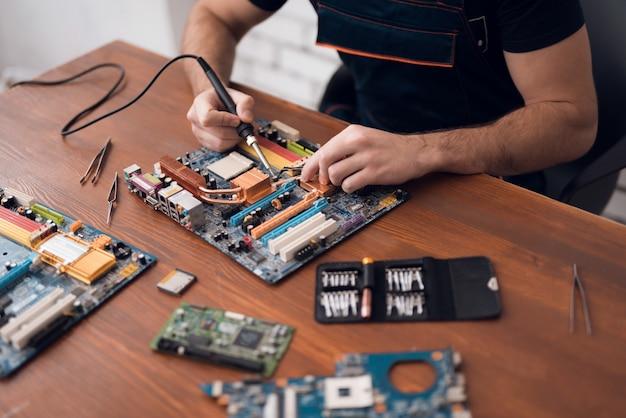 Een man met een soldeerbout repareert computerapparatuur.