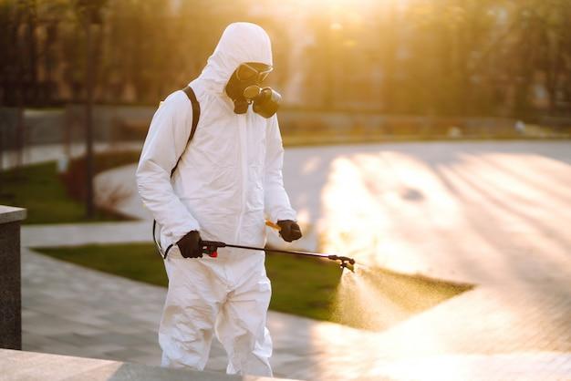 Een man met een speciaal beschermend desinfectiepak spuit sterilisator in de lege openbare ruimte bij zonsopgang in de stad van quarantaine. covid 19. schoonmaak concept.