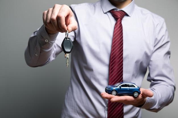 Een man met een speelgoedauto en sleutels in zijn handen.