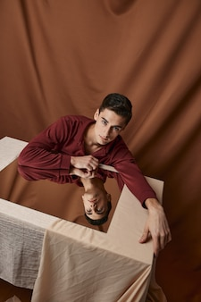 Een man met een spiegel zit aan een tafel op een stoffen achtergrond. hoge kwaliteit foto