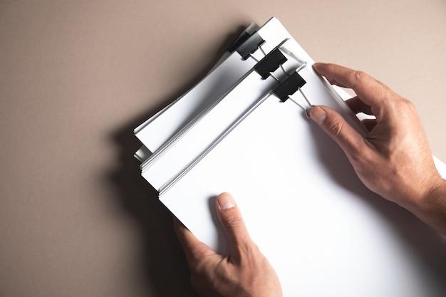 Een man met een stapel papieren op tafel