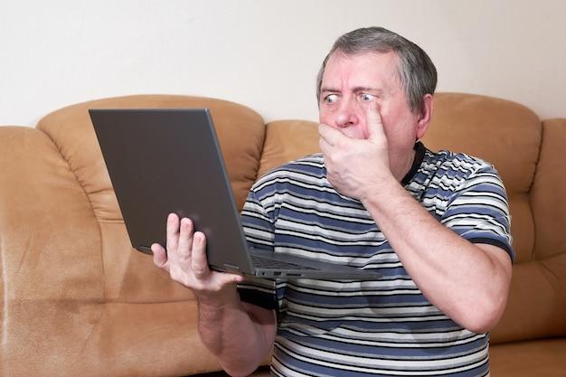 Een man met een verbaasd gezicht houdt een laptop in zijn handen terwijl hij op de bank zit