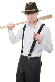 Een man met een vleermuis op zijn schouder rookt een sigaar.