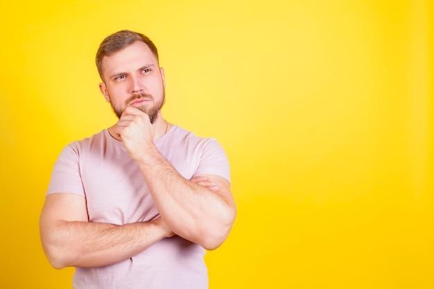 Een man met een vragend, bedachtzaam gezicht, op een gele yak-achtergrond. het concept van besluitvorming, vragen in het hoofd.