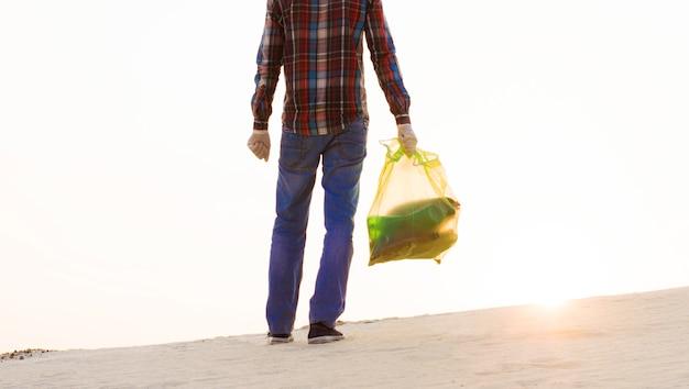 Een man met een vuilniszak maakt het gebied van afval schoon