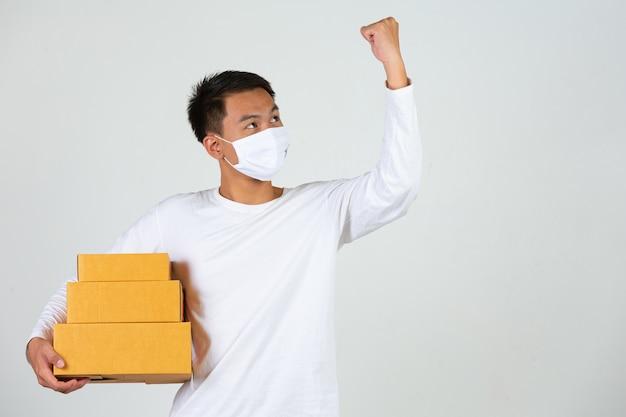 Een man met een wit t-shirt houdt een bruine brievenbus vast om dingen te bezorgen. maak gebaren en gezichtsuitdrukkingen.