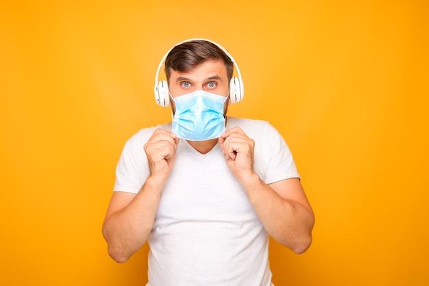 Een man met een witte muzikale koptelefoon staat op een gele achtergrond en draagt een medisch masker.
