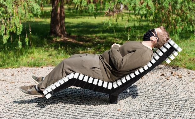 Een man met een zwart beschermend gezichtsmasker zittend op een ligstoel in een park