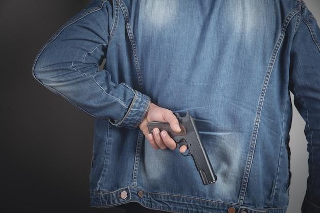 Een man met een zwart pistool in zijn hand dreigt