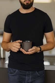 Een man met een zwarte koffie beker in zijn handen