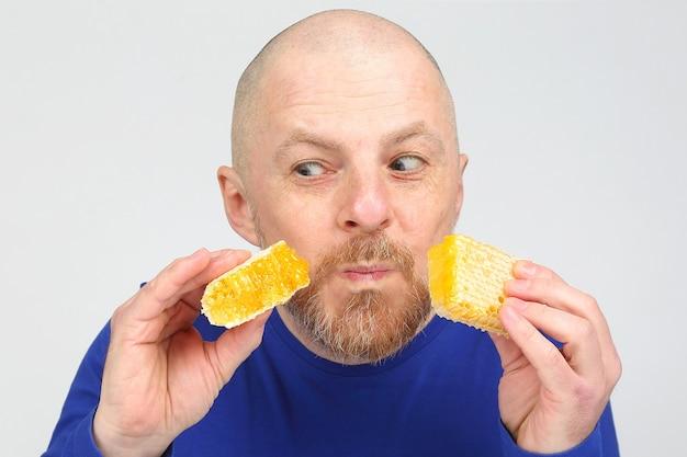 Een man met eetlust kijkt naar twee stukken honingraathoning in zijn handen