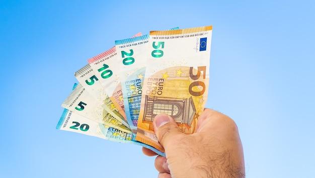 Een man met eurobankbiljetten met blauwe hemelachtergrond