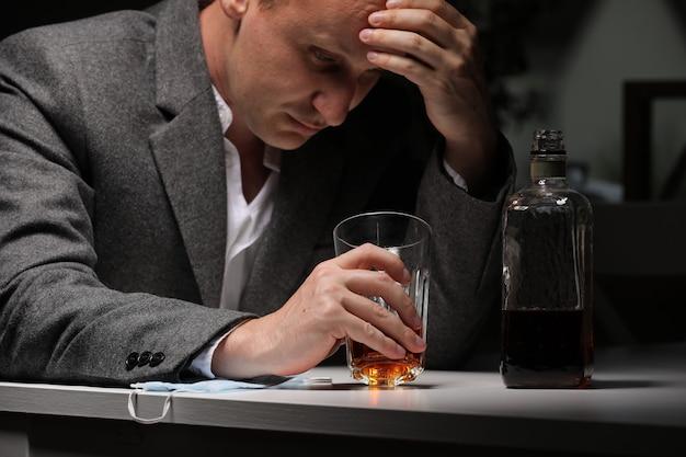 Een man met fles whisky op de keuken. het concept van dronkenschap en alcoholisme. alcoholische vader. een vermoeide zieke man in verdriet drinkt alleen. emotionele ervaring. selectieve aandacht