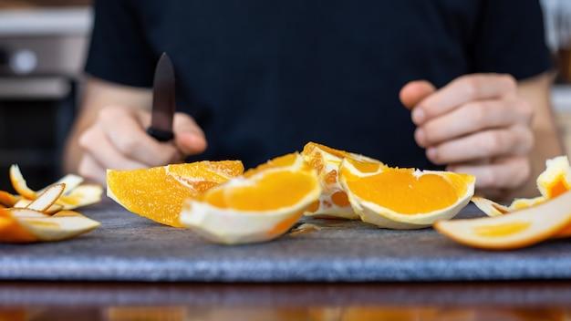 Een man met gesneden sinaasappel op een kookplank en een mes in zijn handen
