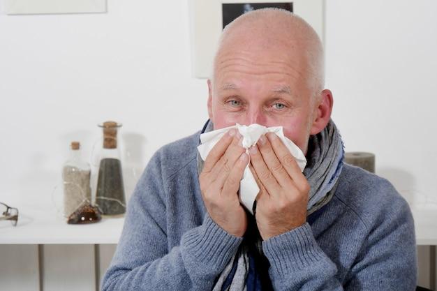 Een man met griep snuit zijn neus