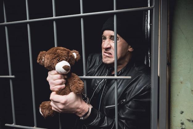 Een man met handboeien zit achter de tralies in een politiebureau.