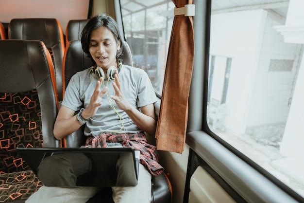Een man met handgebaren en koptelefoon gebruikt een laptop tijdens het chatten via een virtuele vergadering terwijl hij bij een raam in een bus zit