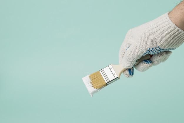 Een man met handschoenen houdt een penseel met druipende witte verf op een blauwe achtergrond. uitvoering van schilderwerken.