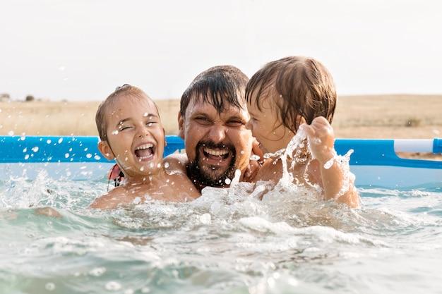 Een man met kinderen die in het zwembad zwemmen, vader met dochter in het water