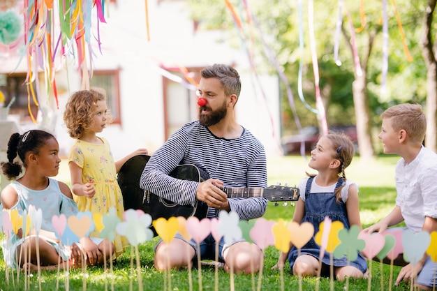Een man met kleine kinderen die in de zomer buiten in de tuin op de grond zit en gitaar speelt.