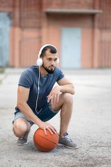 Een man met koptelefoon op straat bereidt zich voor om basketbal te spelen, zittend met een basketbal in zijn hand