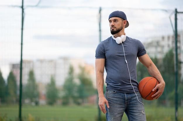 Een man met koptelefoon staat op straat met een basketbal in zijn handen