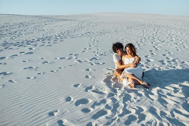 Een man met krullend haar en een mooi meisje hebben plezier op het strand