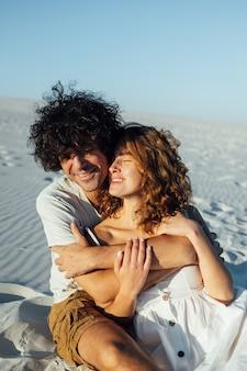 Een man met krullend haar en zijn vriendin knuffelen vrolijk op het zand