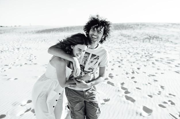 Een man met krullend haar en zijn vriendin knuffelen vrolijk op het zand.