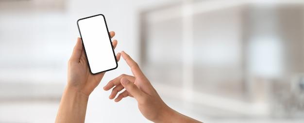 Een man met leeg scherm smartphone in wazig kantoor