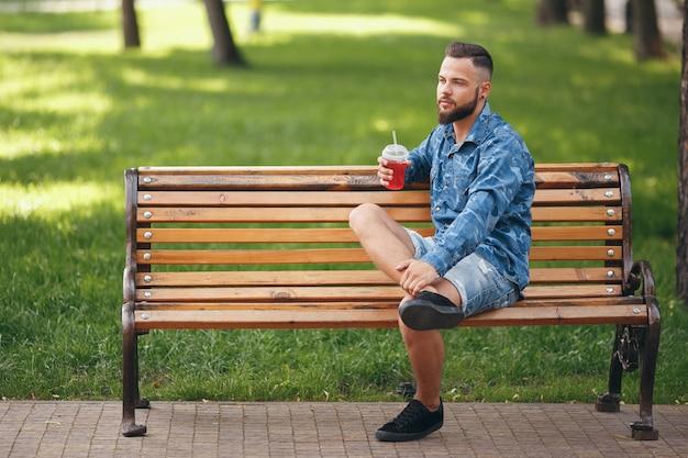 Een man met limonade rust in een park op een bankje in het voorjaar. zonnige dag.